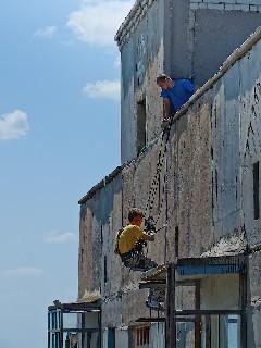 Монтажники высотники утепляют стены в Торезе